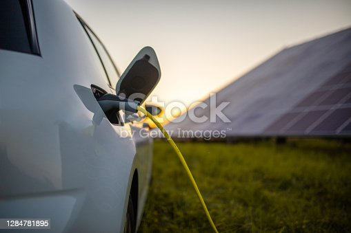 istock Charging electric car and solar panels 1284781895