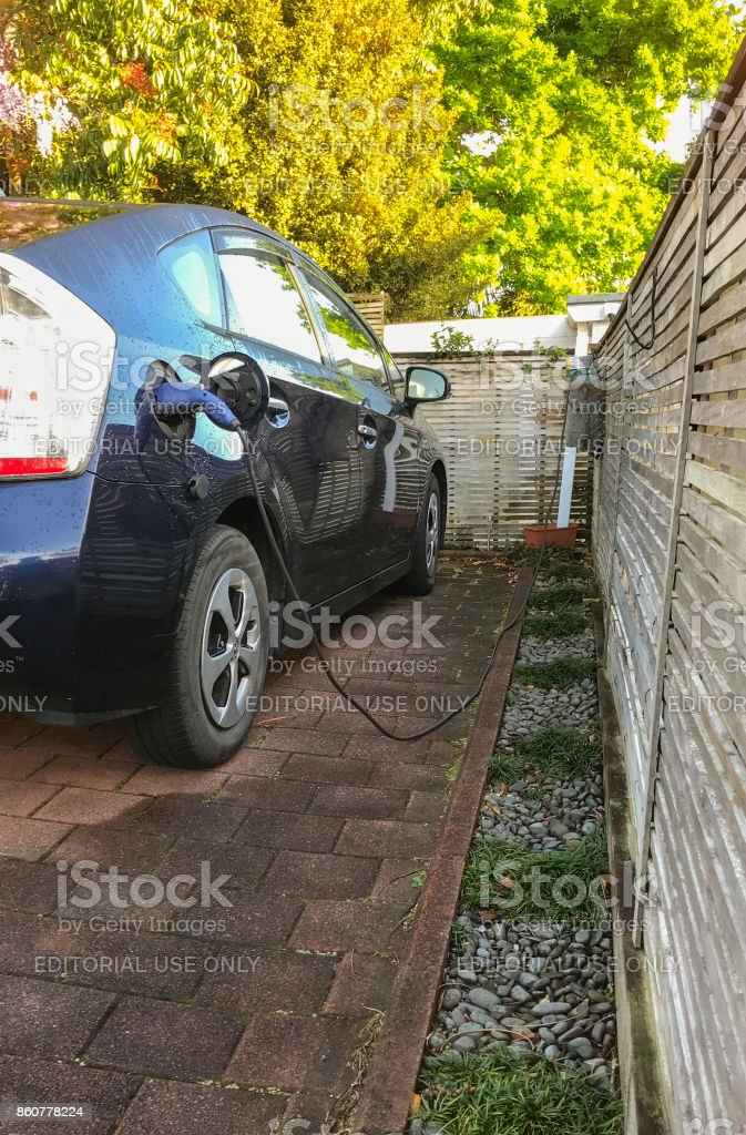 Charging electric car at home in New Zealand stock photo