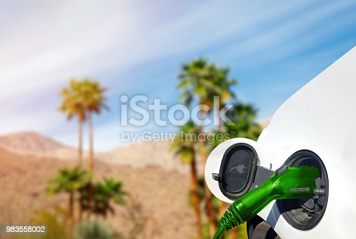 Close up view of Electric Car charging in the desert with palm trees and hills in the background.