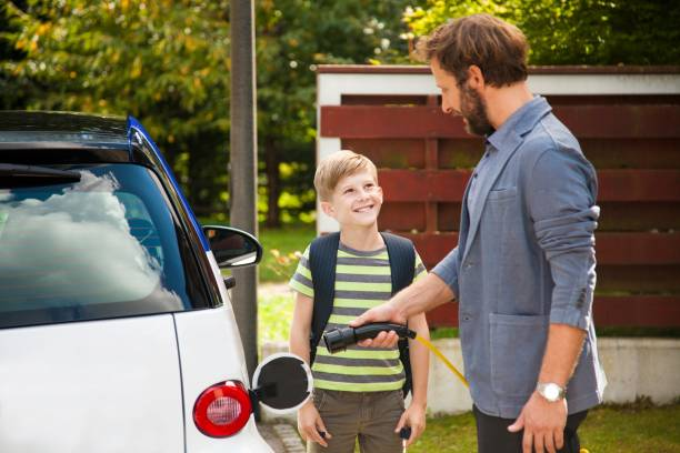 Charging electric car Man charging electric car in domestic garden, boy looking at man and smiling. alternative fuel vehicle stock pictures, royalty-free photos & images