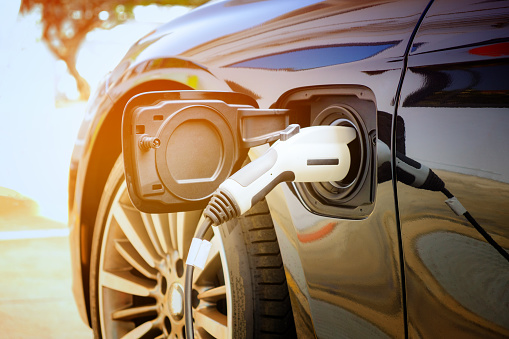 Charging Modern Electric Car Battery On The Street Which Are The Future Of The Automobile Close Up Of Power Supply Plugged Into An Electric Car Being Charged For Hybrid New Era Of Vehicle Fuel Stock Photo - Download Image Now