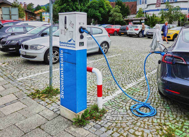 Charging station with connected electric car on a parking lot Garmisch-Parenkirchen, Germany, August 10., 2018: Charging station with connected electric car on a parking lot electro music stock pictures, royalty-free photos & images