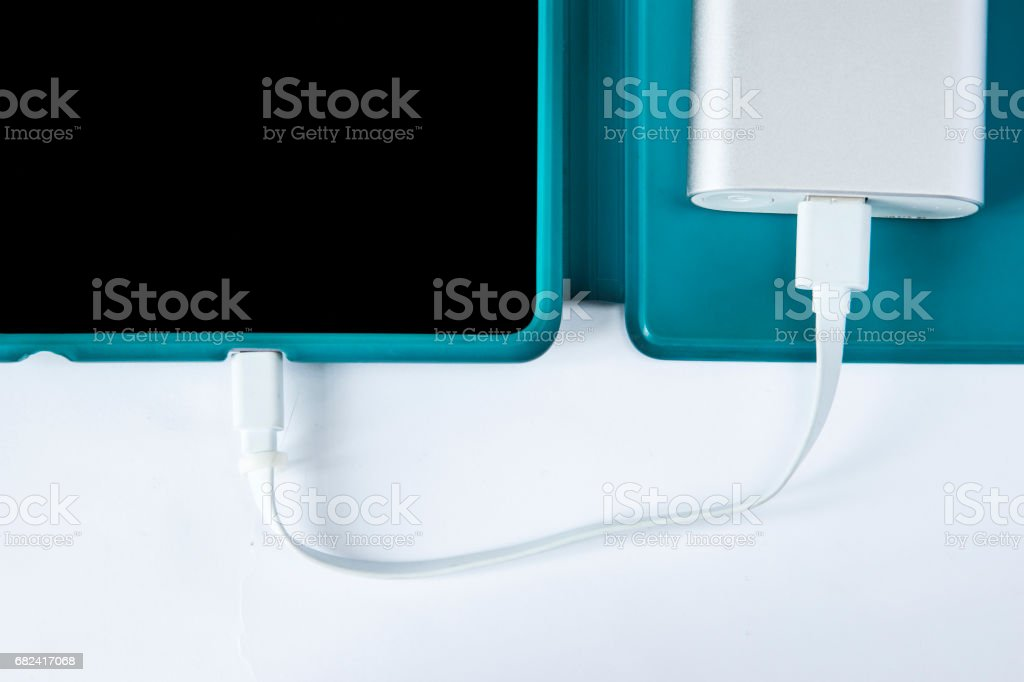 Charging tablet with power bank isolated on white background royalty-free stock photo