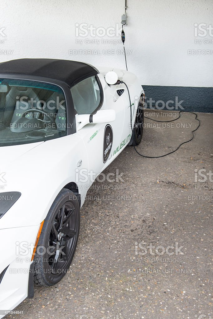 Charging Tesla Roadster sports car stock photo