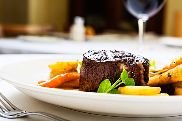 Char-grilled filet  mignon with glazed vegetables A juicy, succulent char-grilled steak accompanied by glazed vegetables and fresh herbs and served with a glass of red wine.  main course stock pictures, royalty-free photos & images