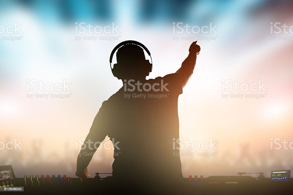 Charismatic disc jockey at the turntable. Charismatic disc jockey. Club, disco DJ playing and mixing music for crowd people. Adult Stock Photo