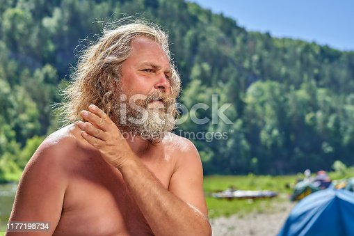 Charismatic grandfather with long hair, mustache and beard. Hand gesture indicates the upper corner of the picture