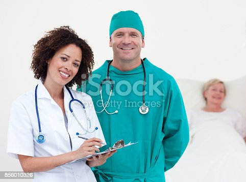 istock Charismatic team of doctors patient lying in her bed 856010326