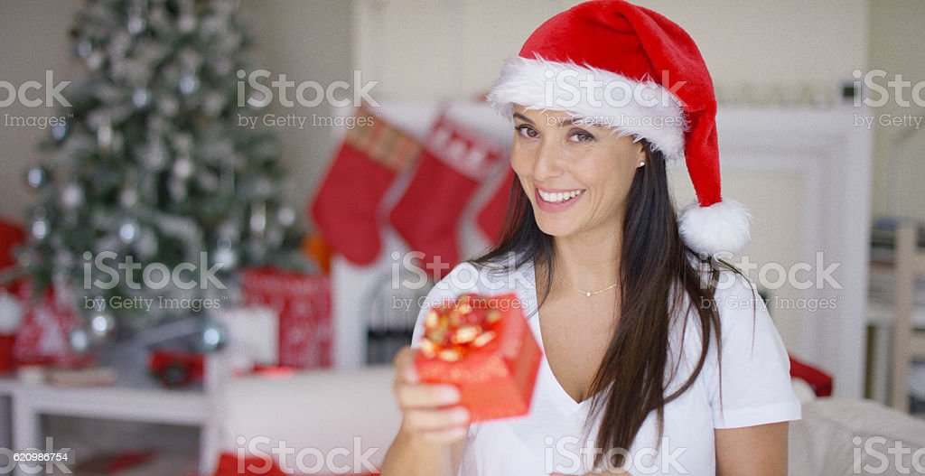 Charismatic young woman holding a Christmas gift foto royalty-free
