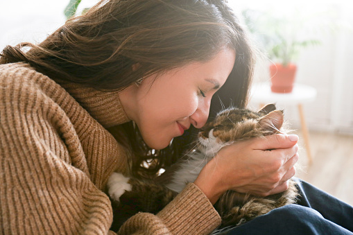 1149249445 istock photo Charismatic young woman playing with her adorable cat. 1205812098