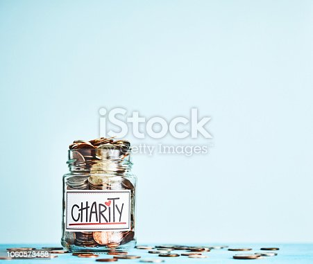 istock Charity American money jar filled with coins with bright blue background 1060573458