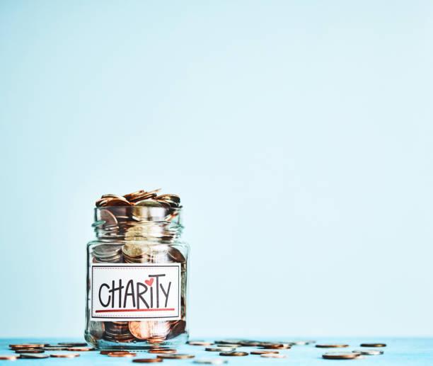 Nächstenliebe amerikanisches Geld Glas gefüllt mit Münzen mit leuchtend blauen Hintergrund – Foto