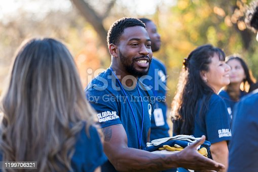 Confident mid adult African American male charity event organizer greets a volunteer during a community cleanup day.