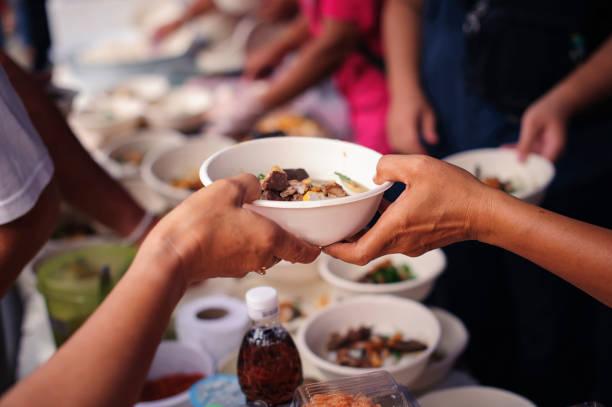 Charity-Lebensmittel sind kostenlos für Menschen in Slums : Hände von Freiwilligen dienen kostenlose Nahrung für die Armen und Bedürftigen in der Stadt – Foto