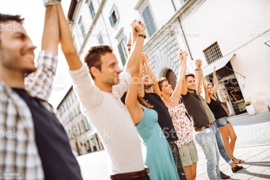 charity friends all togetherness on the city with arm raised stock photo