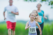 A Caucasian mother, father, and two daughters are outdoors in a field on a sunny day. They are wearing casual athletic clothing and shoes, and they have racing numbers. They are running together towards the camera. One of the daughters is in front.