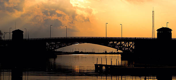Charles Berry Memorial Bridge The Charles Berry Memorial bascule bridge in the Lorain harbor near sunset. Shot from Black River Landing on the East bank of the Black River. bascule bridge stock pictures, royalty-free photos & images