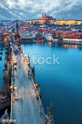 Illuminated Charles Bridge at sunset with people walking over (Prague, Czech Republic).