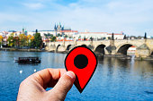 closeup of a young caucasian man with a red marker in his hand pointing the Vltava River and the famous Charles Bridge in Prague, Czech Republic, highlighting the Prague Castle in the background