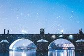Charles Bridge in Prague (Czech Republic) on snowy Christmas evening.