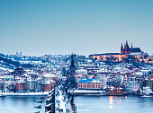 Prague (Czech Republic) with Charles bridge and St. Vitus chatedral on a Christmas evening. People walking over the bridge.