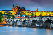 Famous Charles bridge over the Vltava river in Prague at evening. Amazing locations and majestic buildings with colorful lights after sunset, Prague, Czech Republic, Europe