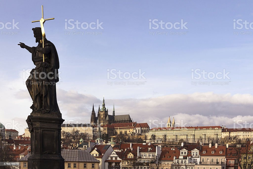 Charles Bridge Statue with shiny cross & St Vitus Cathedral royalty-free stock photo