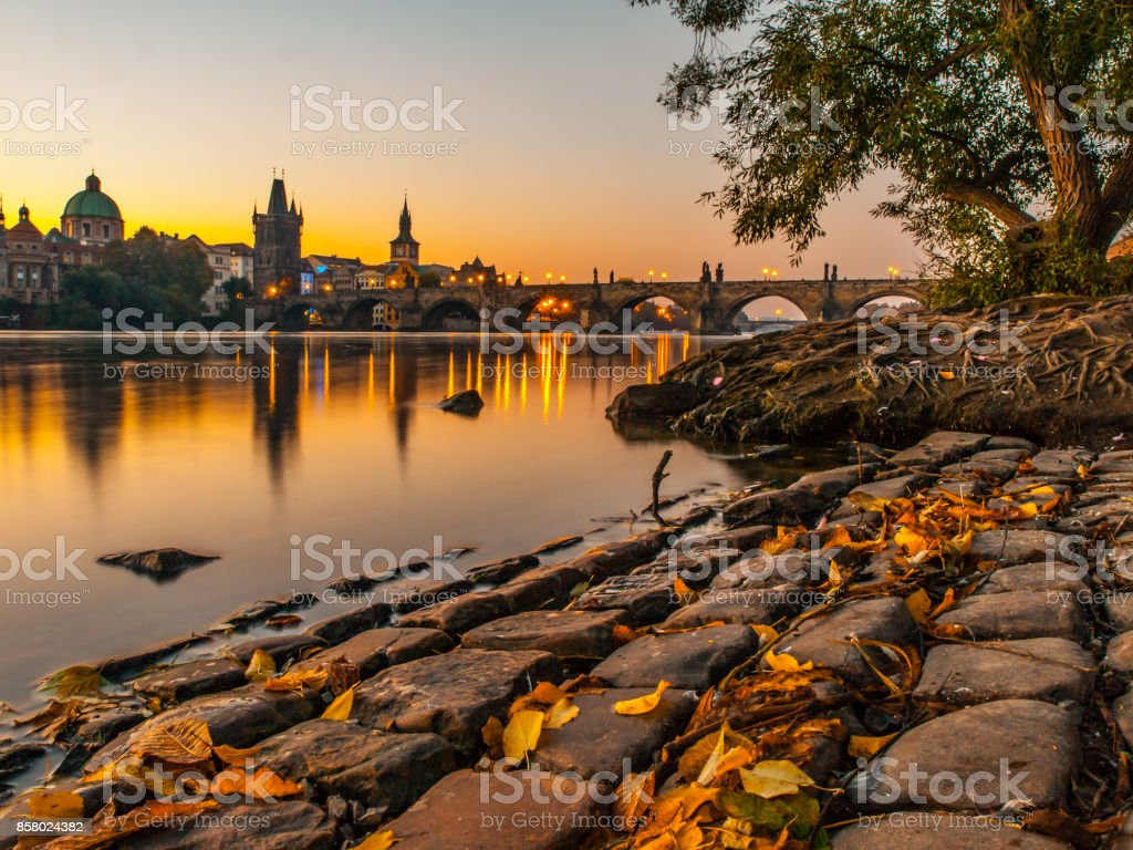Charles Bridge with Old Town Bridge Tower reflected in Vltava River at morning sunrise time, Prague, Czech Republic stock photo