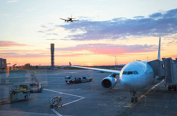 Charles De Gaulle International Airport in Paris at sunrise View of Charles De Gaulle , International airport in Paris -  Airplane at sunrise, with airplanes, one parked and the other taking off, and air traffic control tower. val d'oise stock pictures, royalty-free photos & images
