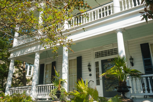 Charleston Colonial Style Porch Home Entrance South Carolina Architecture In Charleston, United States the front door entrance to a residential home in the Colonial Lake neighborhood is surrounded with green plants throughout the exterior porch. southern charm stock pictures, royalty-free photos & images