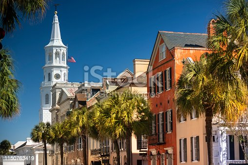 Row of old historic downtown business buildings and Saint Michael's Church on Broad and Meeting streets in Charleston South Carolina USA