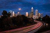The sky starting to light up during the morning rush hour commute in Charlotte, North Carolina. The cars brake lights appear as streaks of red light as they make their way in to the city.