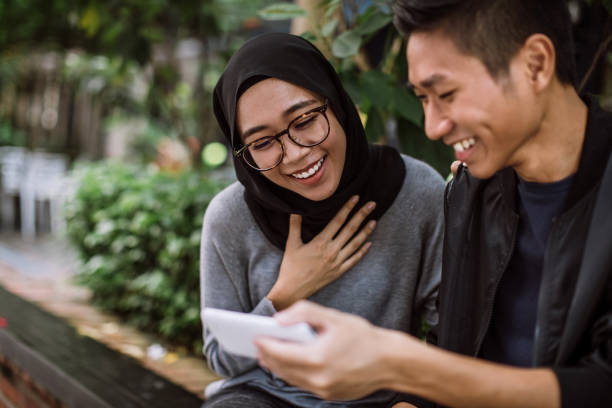 Charmed By Things He's Shown Her On Phone Young Multi-ethnic Couple Went Out On a Date Outdoors. Guy Is Showing His Girlfriend Interesting Things On Internet And She Seems To Be Amazed By It indonesian ethnicity stock pictures, royalty-free photos & images
