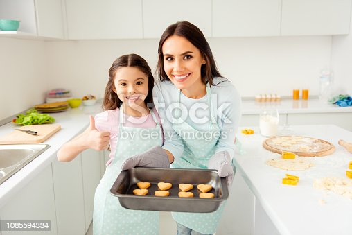 Charming adorable attractive beautiful brunette caucasian kind smiling young mum and her small little offspring daughter, wearing apron, showing thumb up, holding prepared cookies in light kitchen