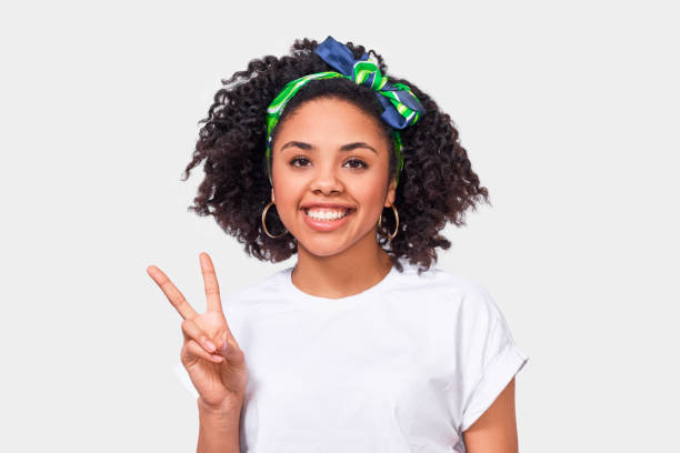 Charming African American young woman smiling broadly, showing peace gesture while looking to the camera, wearing white t-shirt and green headband, standing against white studio background. stock photo