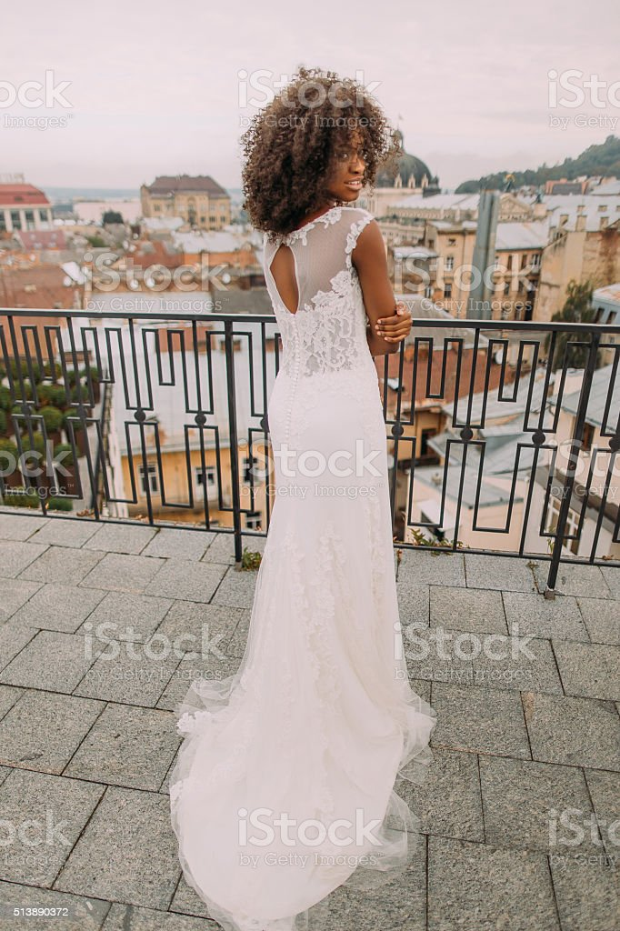 Charming african bride in white lace wedding dress looks over stock photo