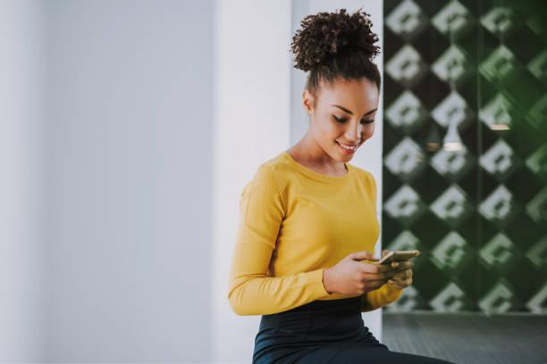 Charmantes afro amerikanisches Mädchen mit Handy im Büro – Foto