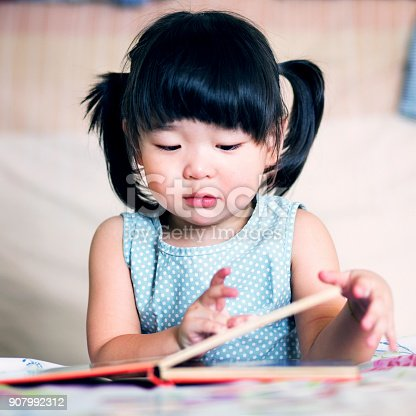 istock Charming and lovely asian kid reading book 907992312