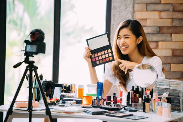 魅力的なアジアの女の子記録ビデオブログカメラの前でメイクアップ化粧品を提示するビューティーブロガー - スタジオ 日本人 ストックフォトと画像