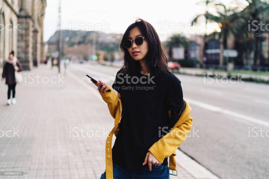 Mujer asiática encantadora en gafas de sol usando blanco camiseta negra y  chaqueta de cuero amarilla 30a30397a471