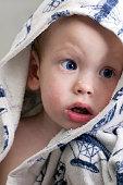 Charming baby boy in a blue bathrobe with a hood