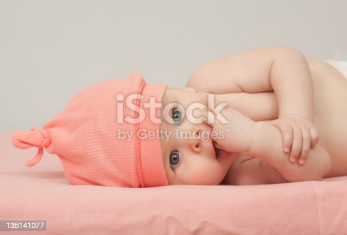 Baby girl in pink hat lies on back and sucks her fingers