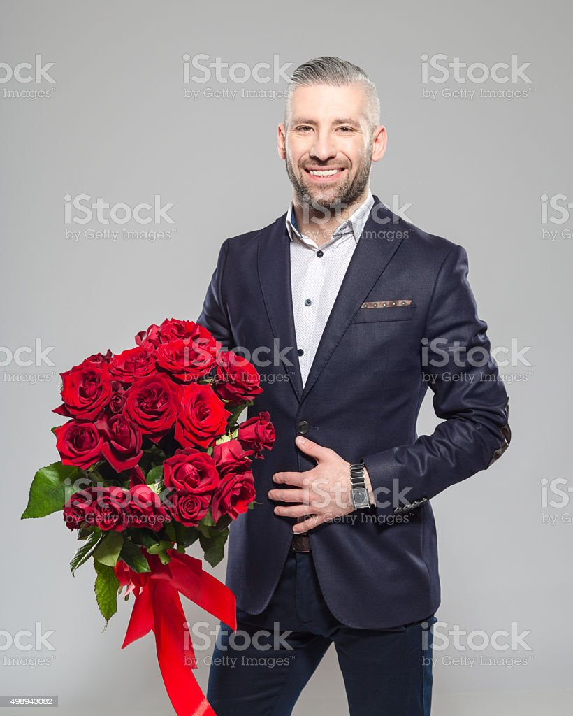 Charming bearded grey hair businessman holding bunch of roses Portrait of elegant bearded grey hair businessman standing against grey background, holding a bunch of red roses, smiling at camera. Studio shot, one person.  2015 Stock Photo