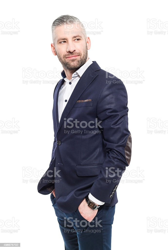 Charming bearded grey hair businessman Portrait of elegant bearded grey hair businessman standing against white background with hands in pockets. Studio shot, one person.  2015 Stock Photo
