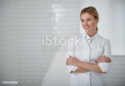 Waist up portrait of young cosmetologist in white lab coat looking away with smile. Copy space on left side
