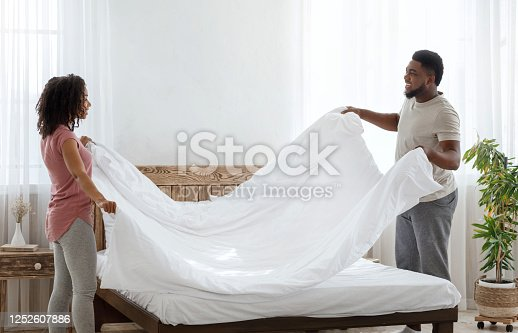 Family domestic chores. Charming african-american couple in love making bed together, free space