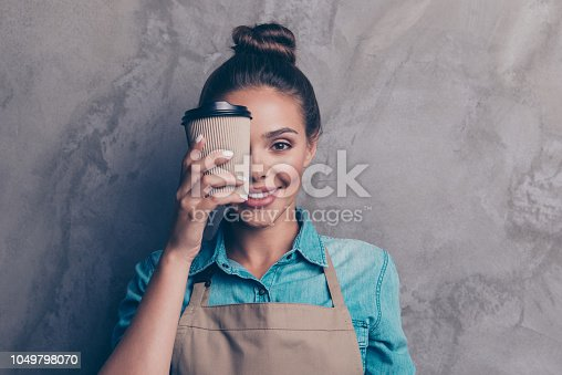 istock Charming, beautiful girl holding drink in front of her close half face and smile isolated on gray textured wall background 1049798070