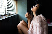 istock Charming beautiful sexy woman is smoking marijuana or cigarette. Attractive beautiful girl feel relaxing and happiness. She feel absent minded or in a dreamy state. Beautiful asian woman wear fur coat 1092078386