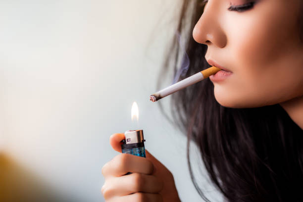 Charming beautiful young asian woman use cigarette lighter for lighting cigarette in her house. Attractive beautiful lady smokes the cigarette because she gets stressed, nicotine make relieve stress stock photo