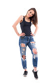 istock Charming beautiful young female fashion model in ripped jeans posing and smiling at camera. 1069248980